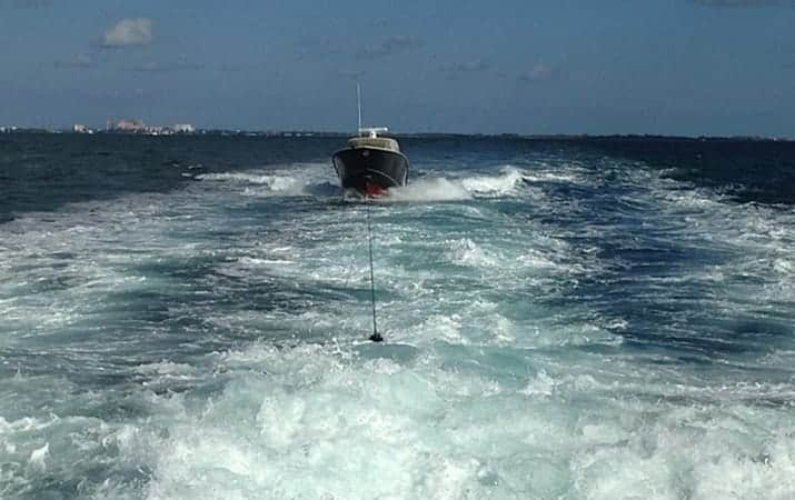 Scout being towed behind a yacht